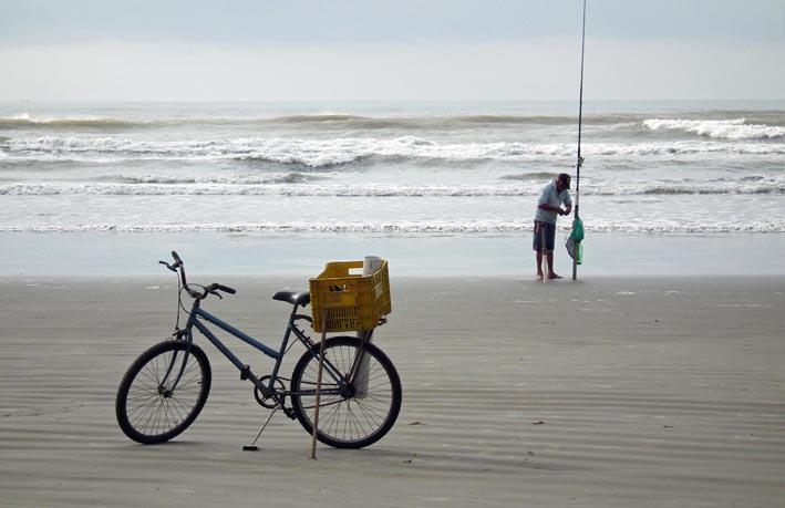 Fiets met krat en koker voor visspullen en visser aan het strand