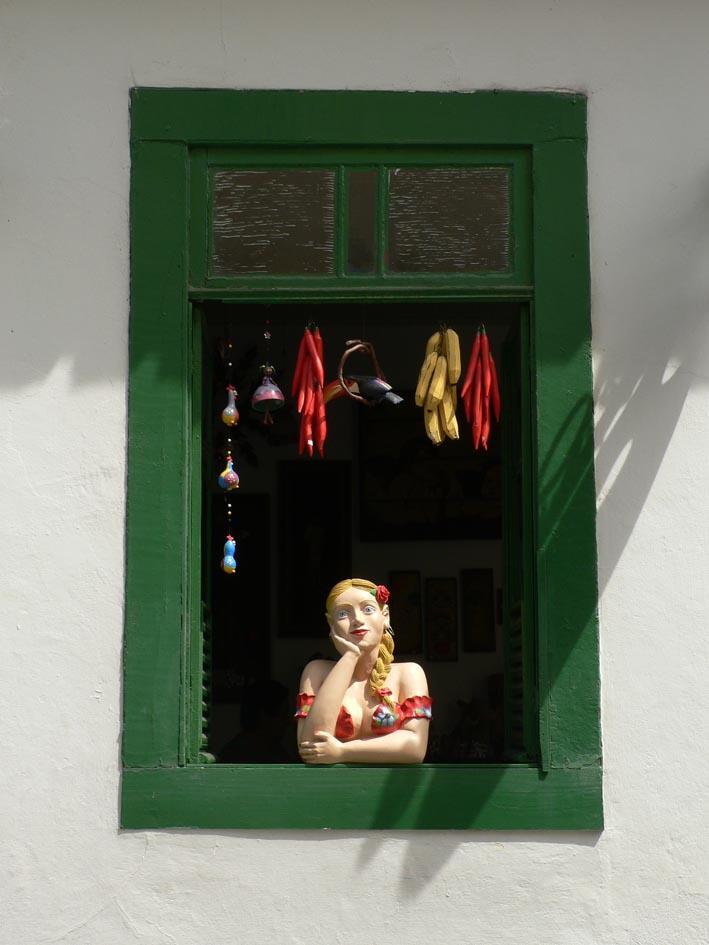 Beeld vrouw, hand onder kin uitkijkend uit raam