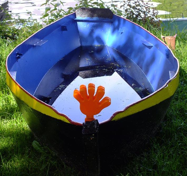 Kleurig bootje op wal, oranje hand op boeg