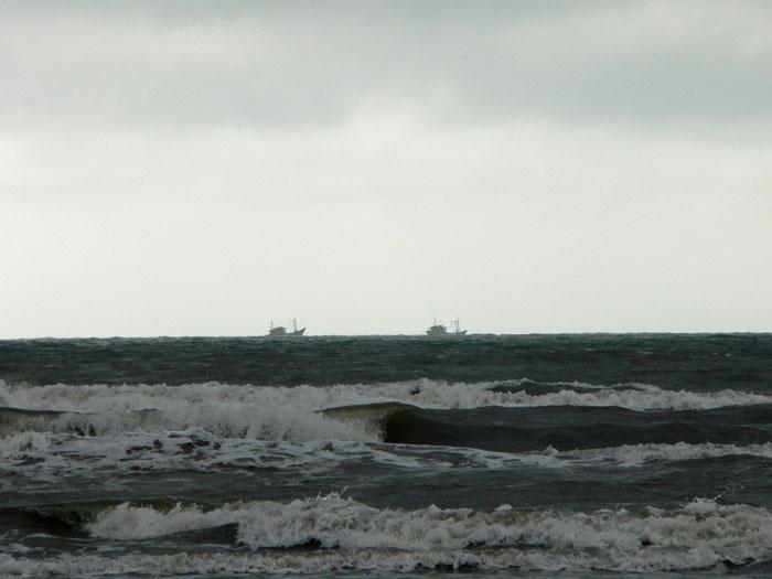 Foto visserschepen aan horizon onder donkere lucht