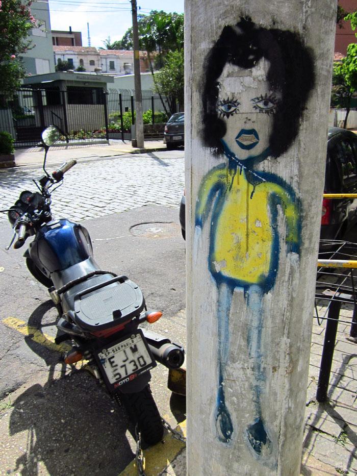 Foto vrouwspersoon geschilderd op paal naast geparkeerde motorfiets