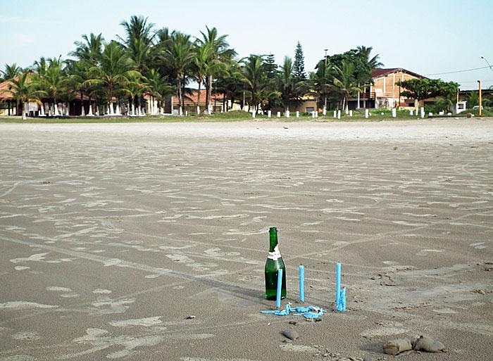 Foto van fles en kaarsen op strand