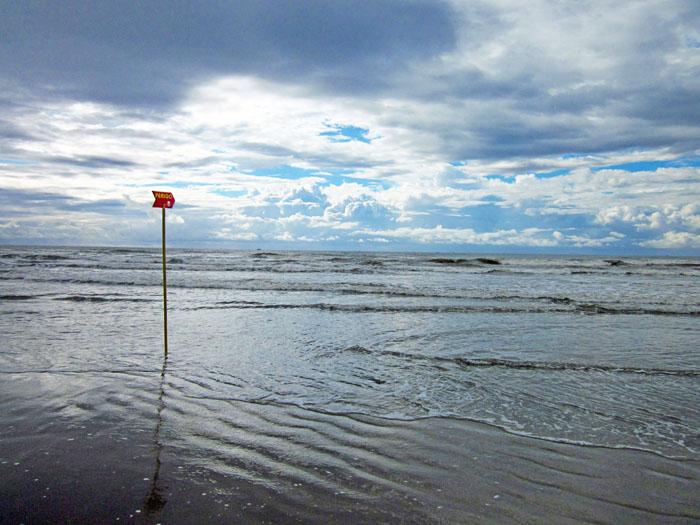 Foto zee met wolkenlucht en bordje 'gevaar'