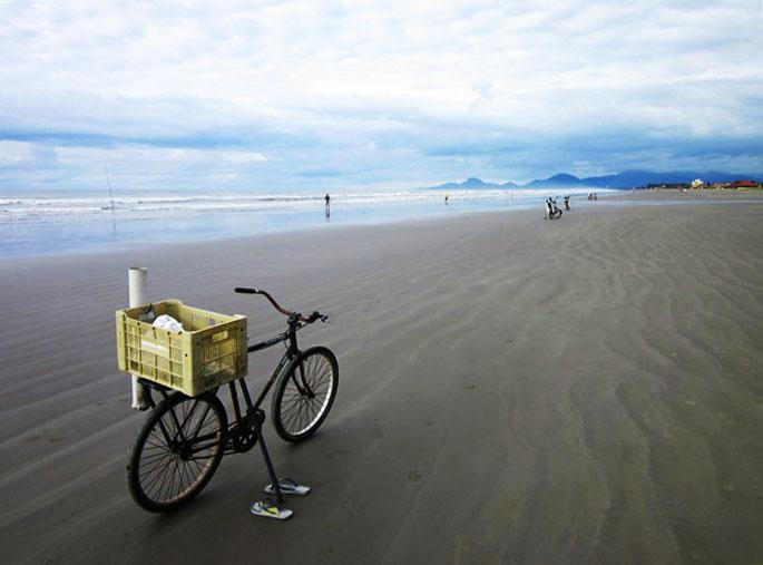 Foto fiets met visbenodigdheden op strand