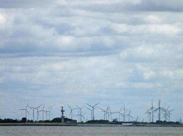 Foto windmolenpark aan de overkant van het water, wolkenlucht