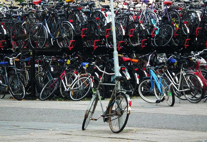 Foto van fiets tegen paal en volle fietsenrekken