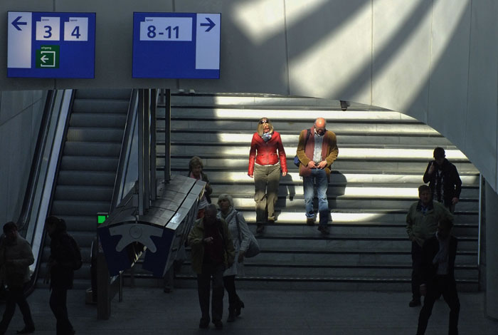 Foto passagiers op trappen station Arnhem, zonlicht en schaduw