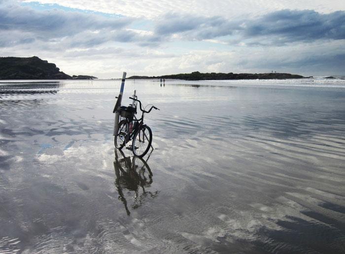 Foto van een fiets op een nat en spiegelend strand
