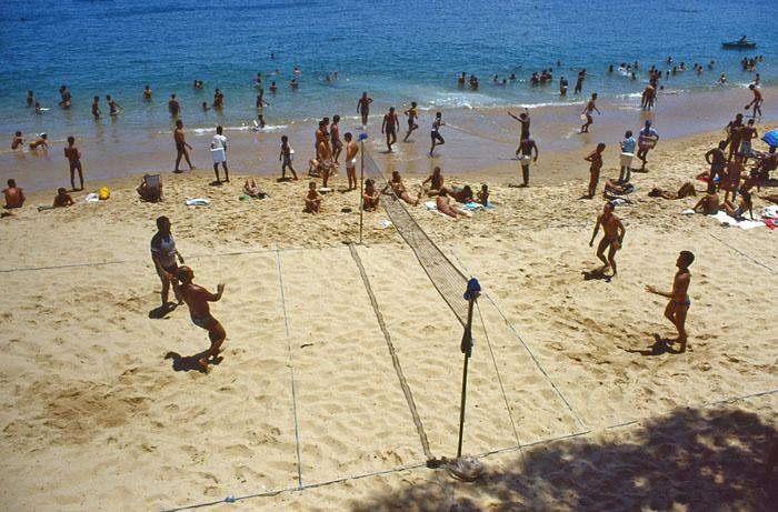 Foto strand met badgasten en volleyballers