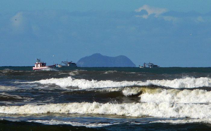 Foto van drie vissersboten voor de kust