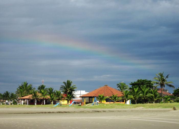 Foto van regenboog boven strandpaviljoen