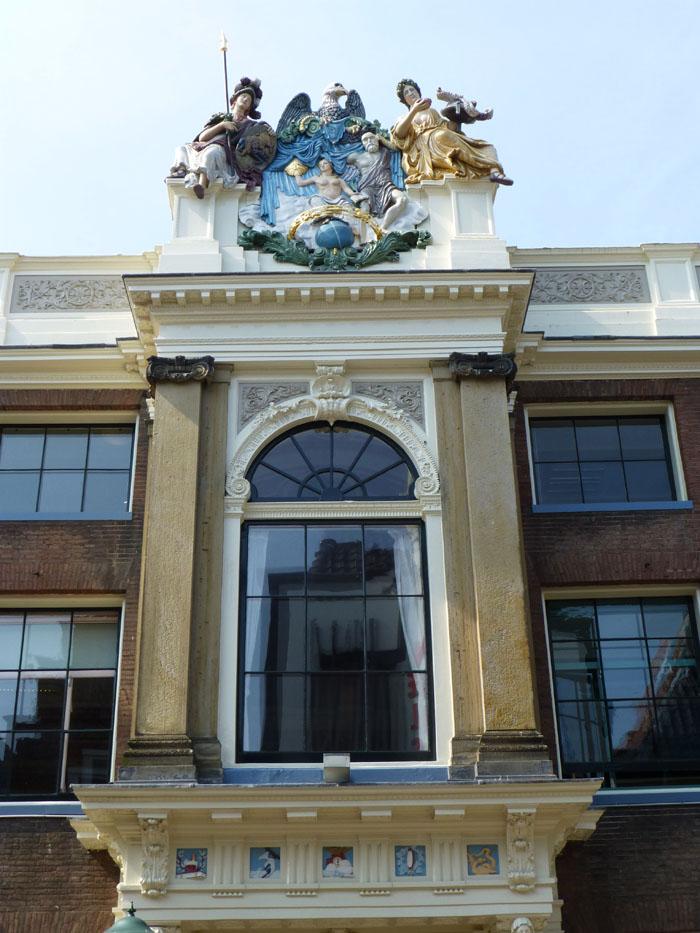 Foto van gevel met groot raam en beeldenpartij