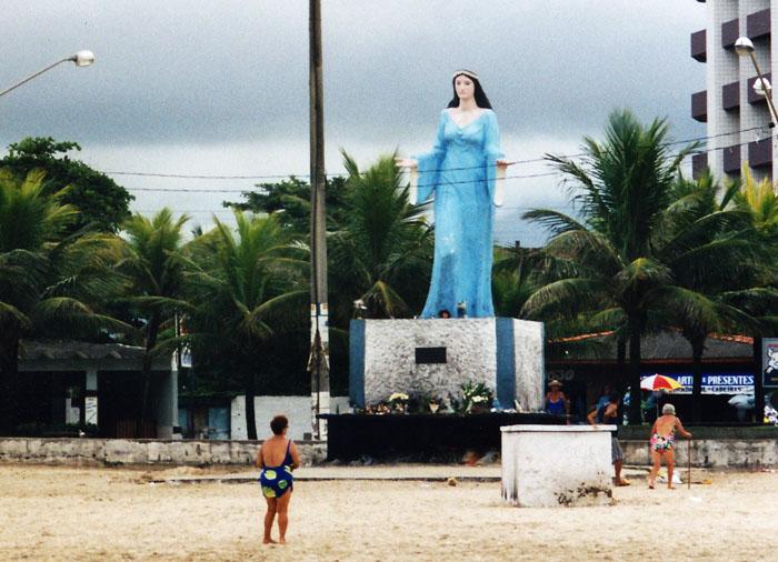 Foto van vrouw biddend voor beeld Iemanjá op strand