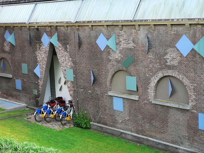 Foto van muur met artsitieke elementen en gekleurde fietsen