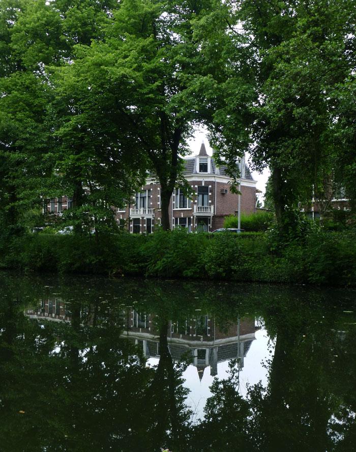 Foto van herenhuis gezien tussen de bomen aan het water