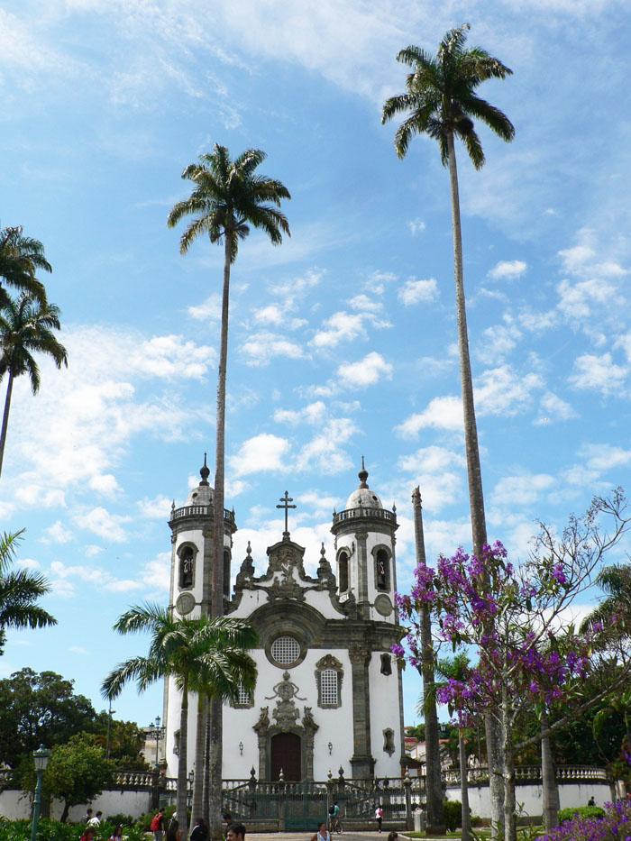 Foto van kerkje tussen hoge palmbomen
