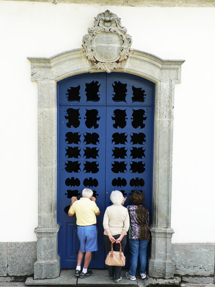 Foto van toeristen die door een kapeldeur naar binnen kijken