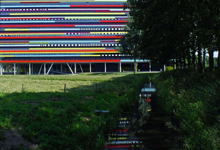 Foto van veelkleurig gebouw met reflectie in sloot