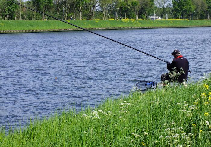 Foto van visser aan kanaal