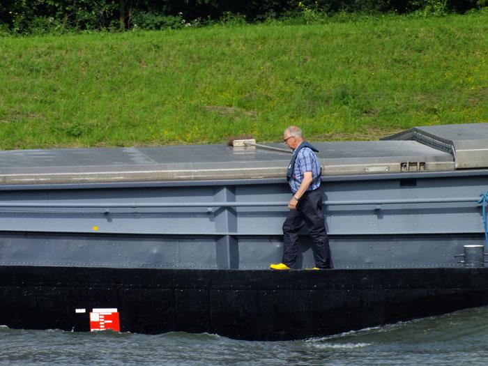Foto van man lopend over varende vrachtboot op kanaal