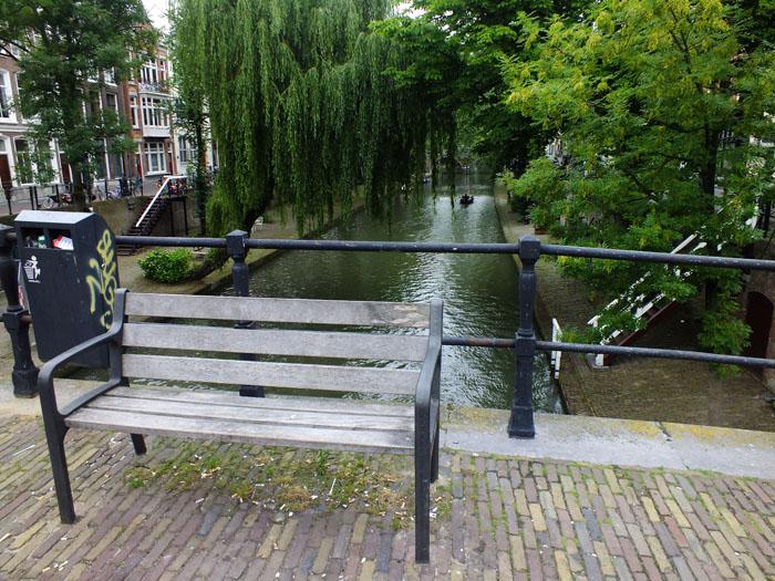 Foto van bankje op brug over gracht met bomen