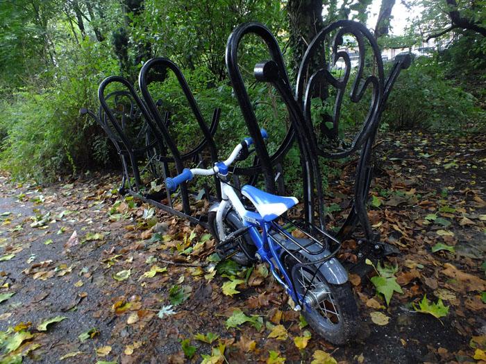 Foto van klein blauw fietsje tegen fietsenrek