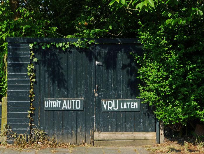 Foto van houten deuren met opschrift 'Uitrit auto vrij laten'