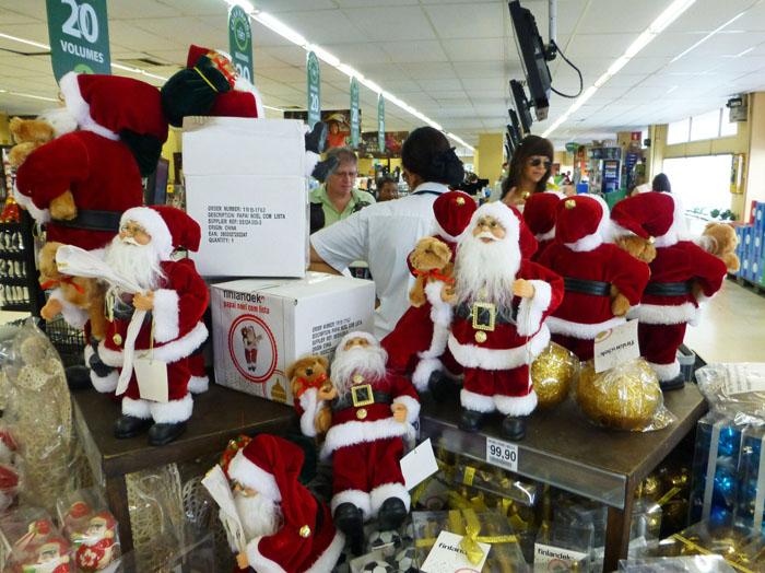Foto van kerstmanpoppen met beertje onder arm in supermarkt