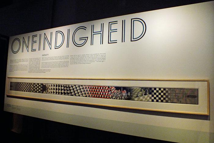 Foto van poster met titel Oneindigheid boven Metamorfose II van M.C. Escher