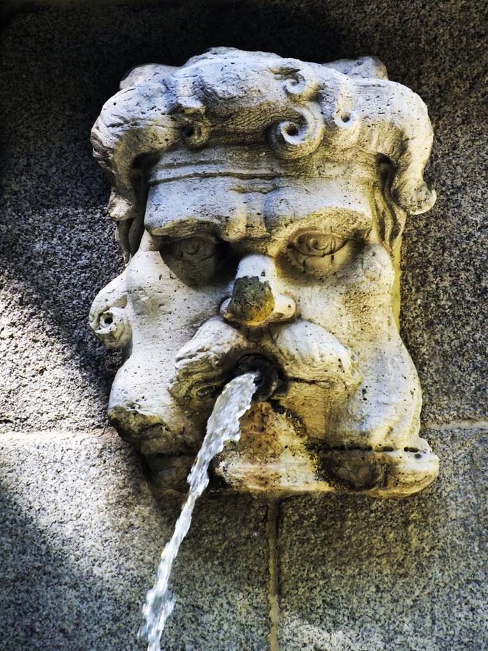 Foto van gebeeldhouwde mannenkop die water spuit
