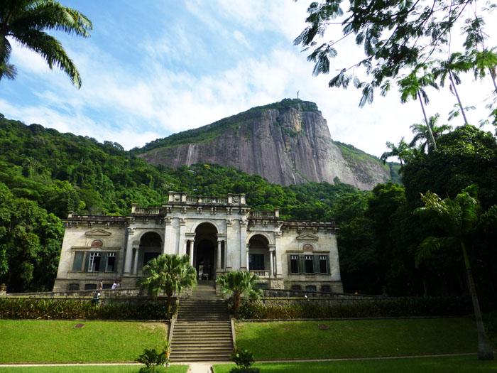 Foto buitenhuis tegen achtergrond van berg met Christusbeeld