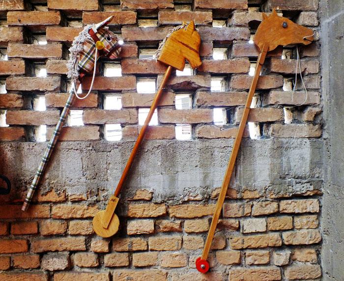Foto van drie stokpaardjes aan muur