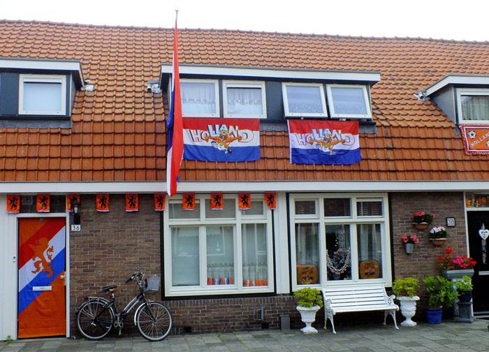 Foto van huizen met vlaggen en oranje versiering