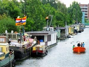 Foto van rij woonboten met vlag en oranje bootje op kanaal
