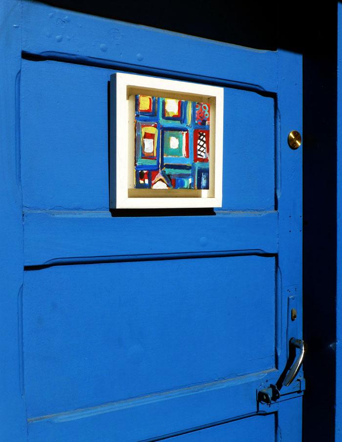 Foto van schilderijtje op blauwe deur