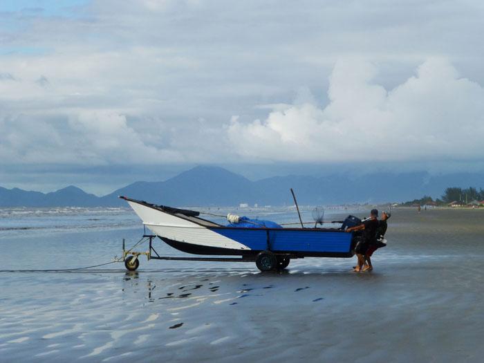 Foto van vissres die boot het strand op trekken