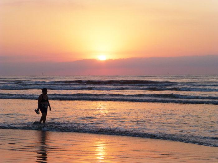 Foto van wandelaar aan het strand bij zonsopgang