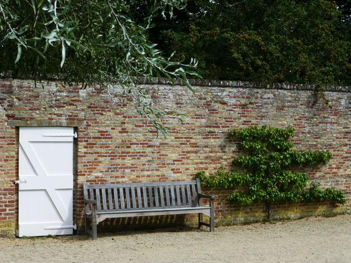 Foto van muur met deur, bank en struik