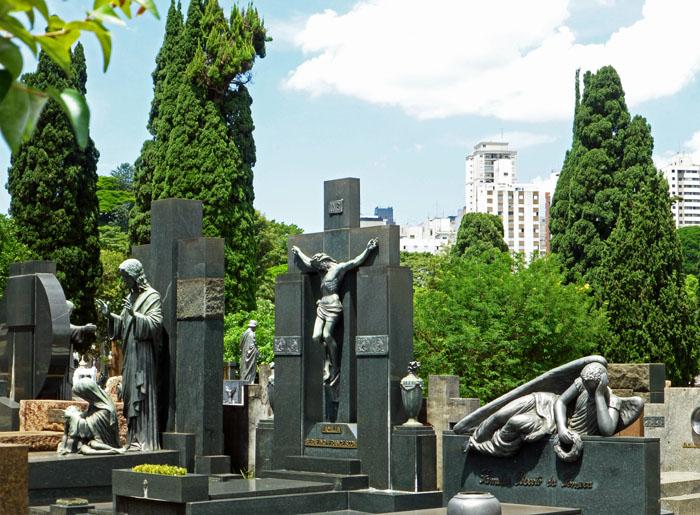 Foto van begraafplaats met bomen en flats op achtergrond