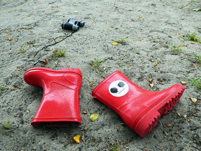 Foto van rode laarsjes en verrekijker in het zand