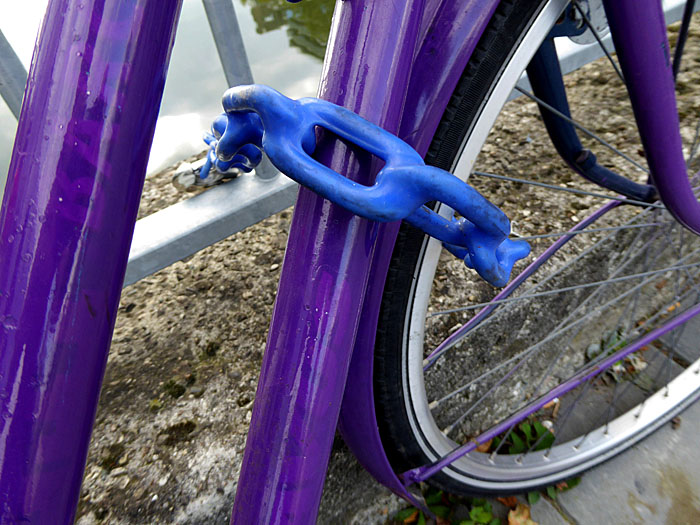 Foto van paarse fiets met blauw geplastificeerd kettingslot