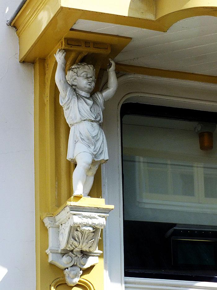 Foto van beeldje van kind (engeltje?) dat balkon steunt