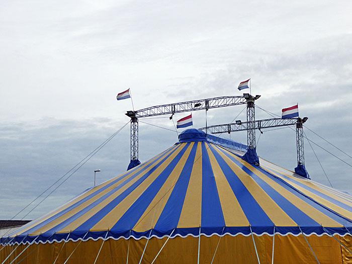 Foto van gestreepte circustent met vlaggen