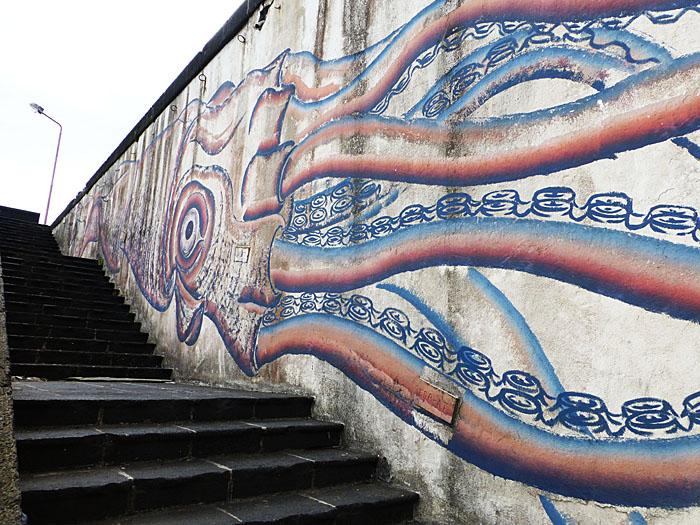 Foto van afbeelding van grote inktvis op muur bij trap