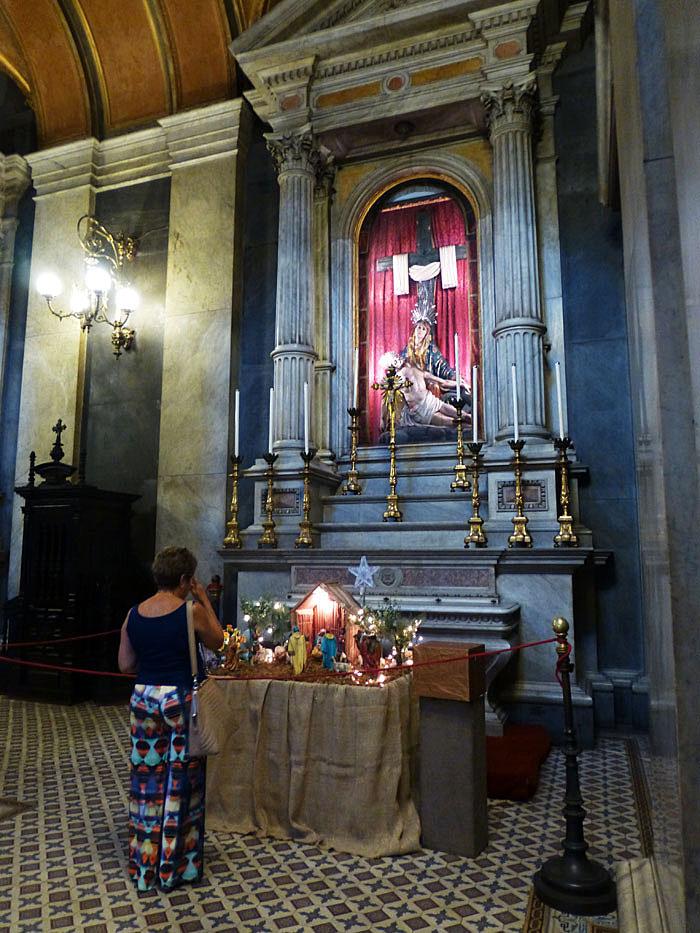 Foto van vrouw biddend voor kerststal