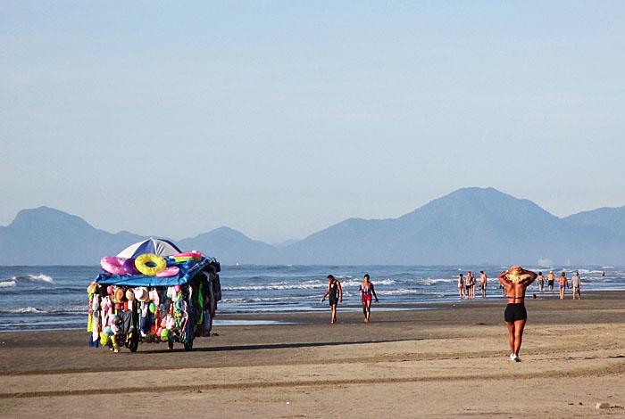 Foto van strand met ambulante verkoper en wandelaars