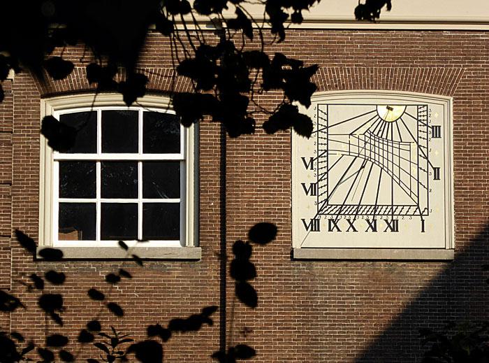 Foto van venster en zonnewijzer