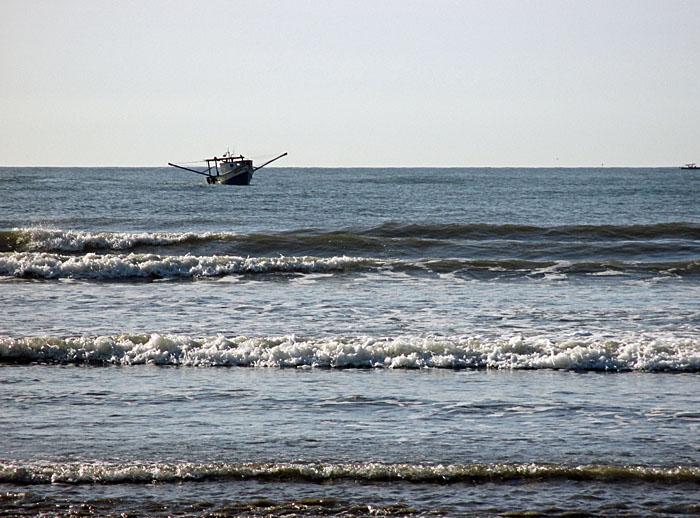 Foto van bootje voor de kust