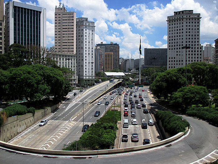 Foto van brede verkeersstraat en flatgebouwen