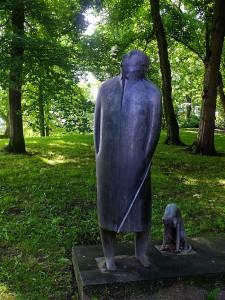 Foto van standbeeld van omhoog kijkende heer met hondje